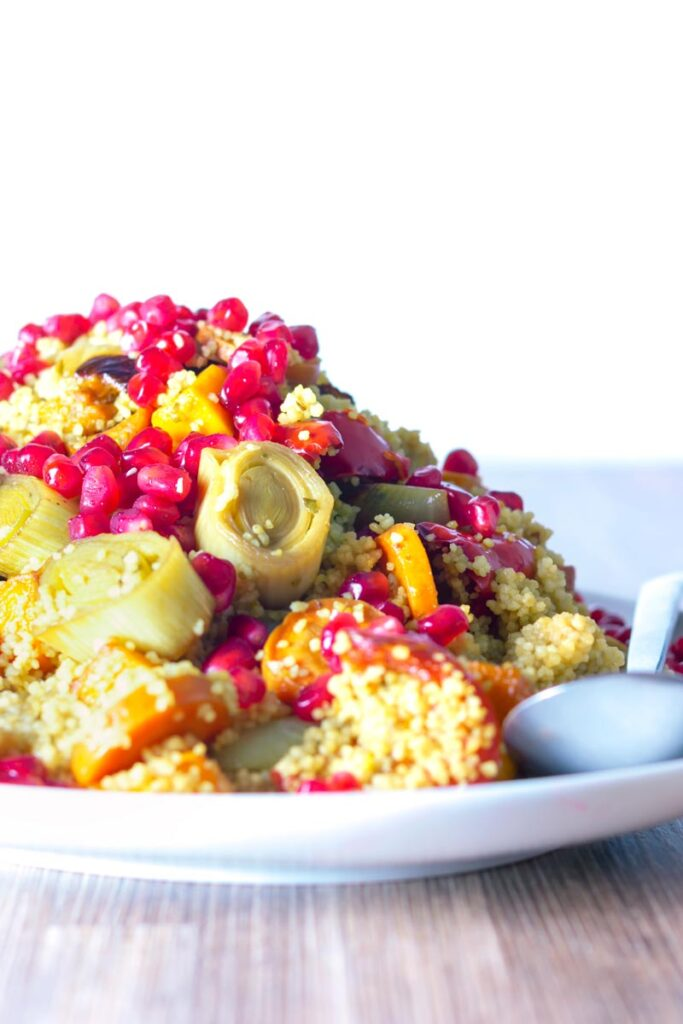 Portrait image of a roasted vegetable couscous salad with pomegranate seeds served on a large serving platter