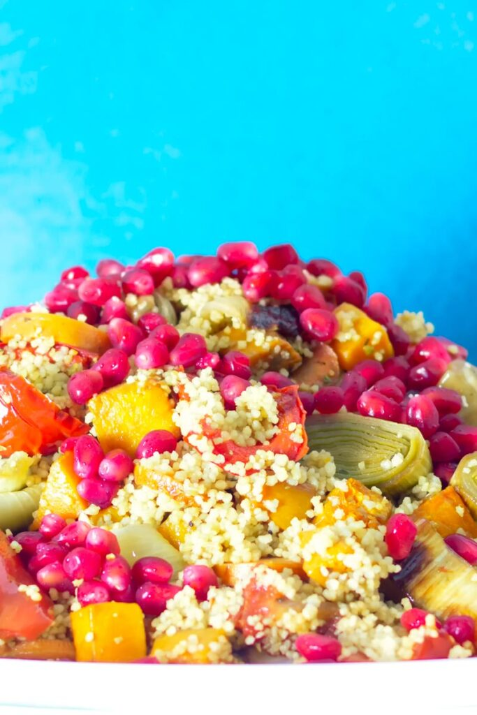 Portrait close up image of a roasted vegetable couscous salad with pomegranate seeds