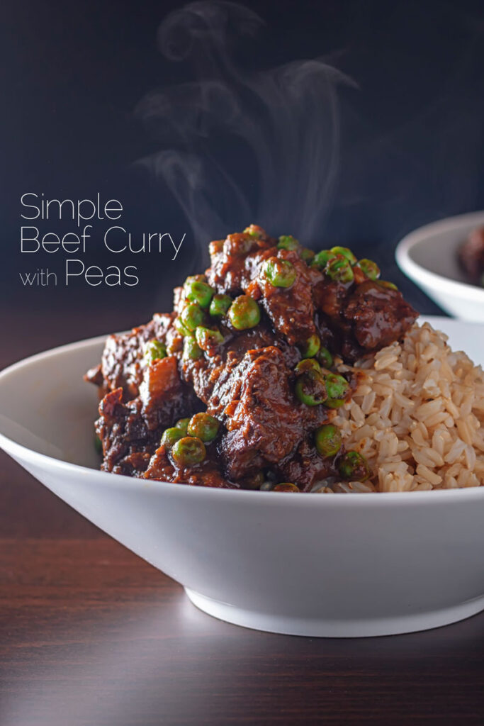 Portrait image of a steaming bowl of a simple rich beef curry with peas with text overlay