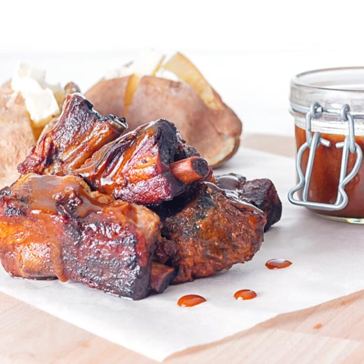 Square close up char siu pork ribs that have been cooked in a slow cooker served with baked potatoes and a jar of sauce