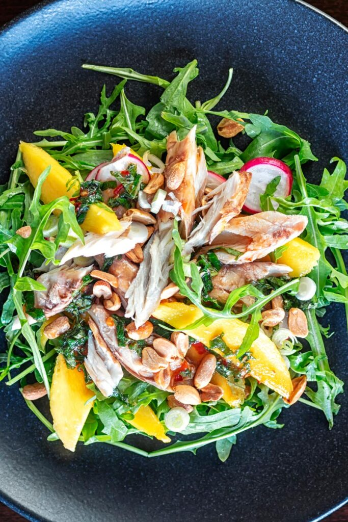 Portrait overhead image of a  mackerel salad featuring mango, peanuts, rocket and spring onions served on a black plate