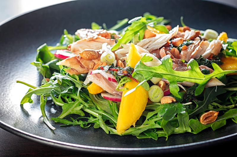 Landscape image of a mackerel salad featuring mango, peanuts, rocket and spring onions served on a black plate
