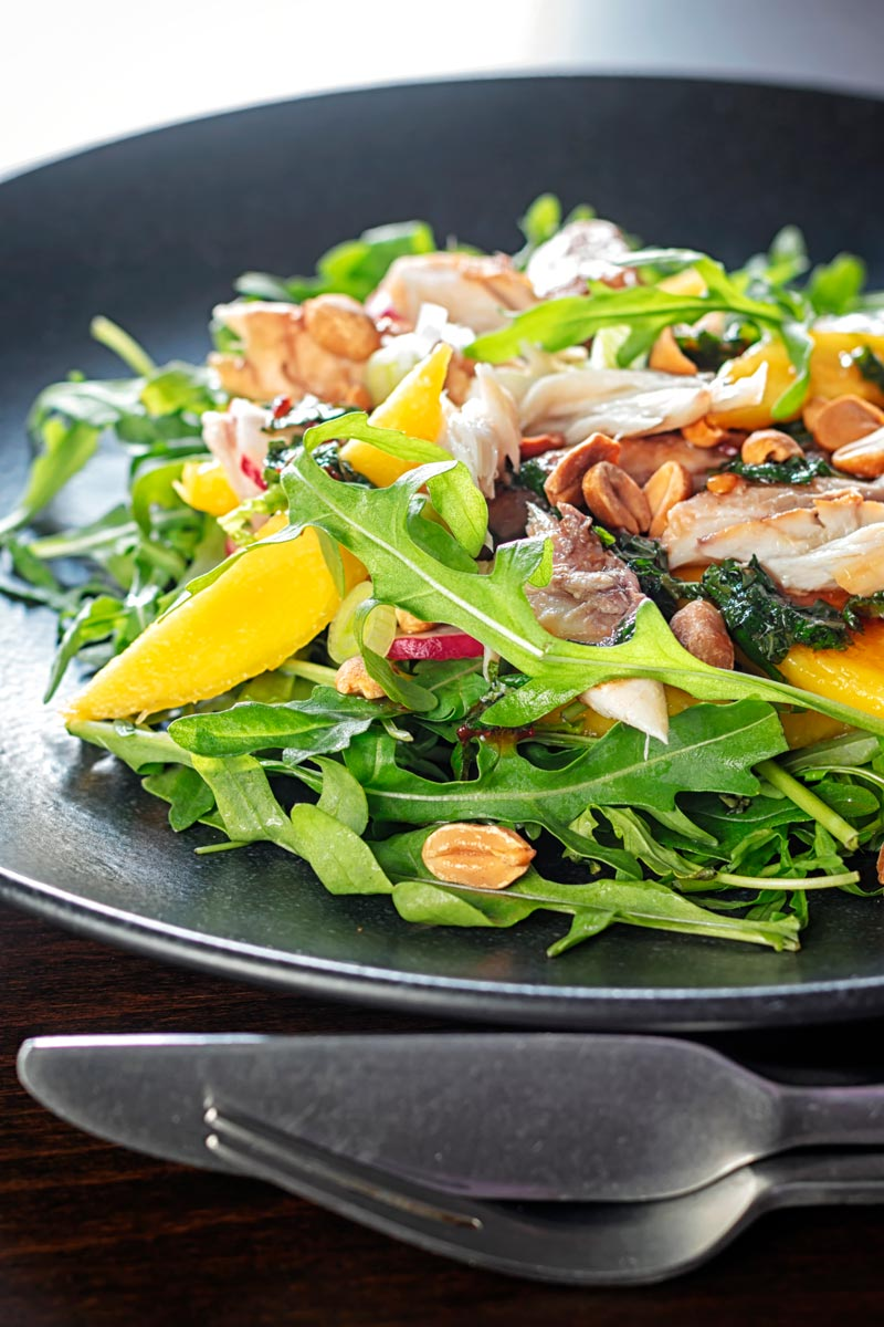 Portrait image of a smoked mackerel salad featuring mango, peanuts, rocket and spring onions served on a black plate