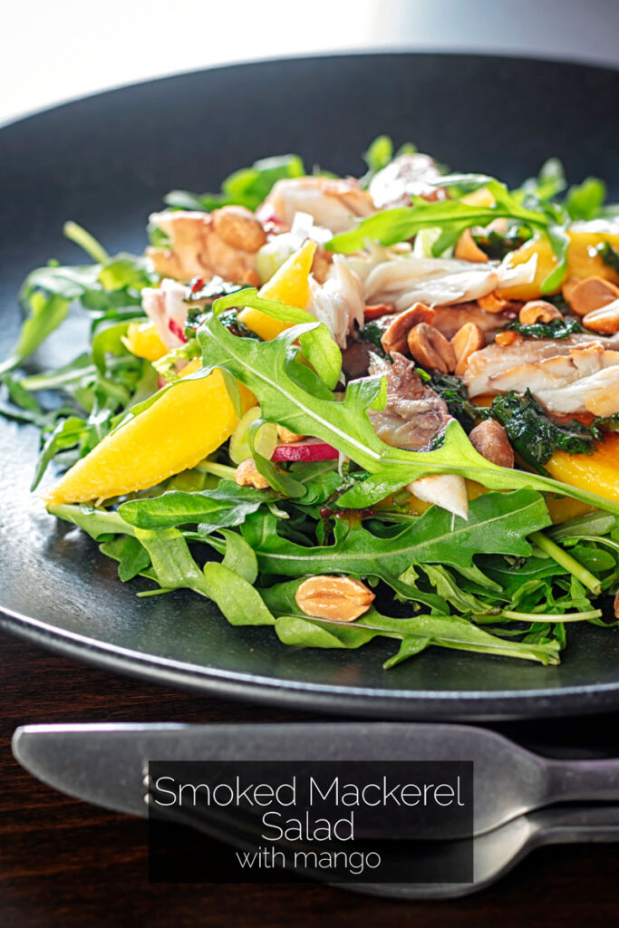 Portrait image of a smoked mackerel salad featuring mango, peanuts, rocket and spring onions served on a black plate with text overlay