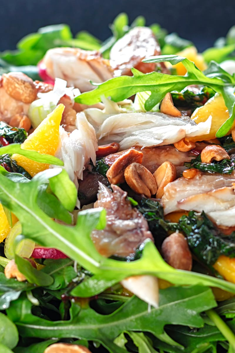 Portrait close up image of a smoked mackerel salad featuring mango, peanuts, rocket and spring onions