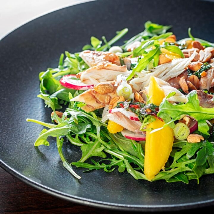 Square image of a smoked mackerel salad featuring mango, peanuts, rocket and spring onions served on a black plate