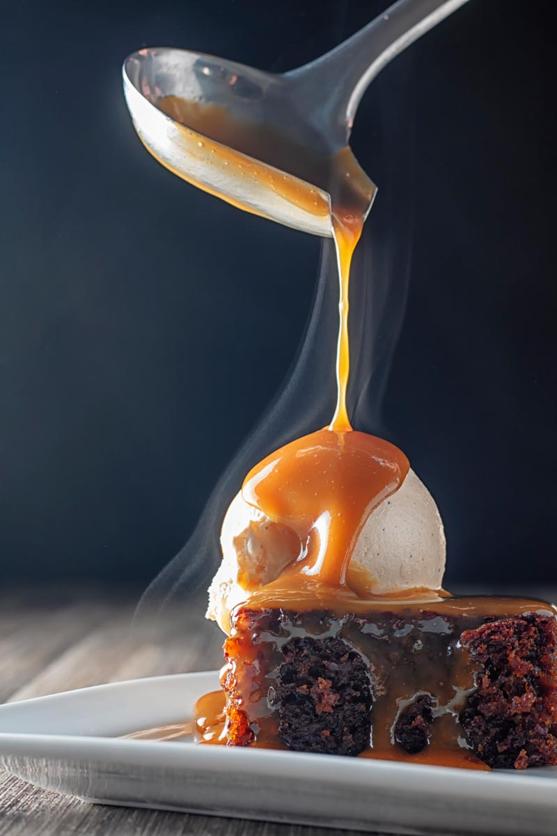 Portrait image of a steaming hot caramel sauce being poured over a sticky toffee pudding topped with vanilla ice cream