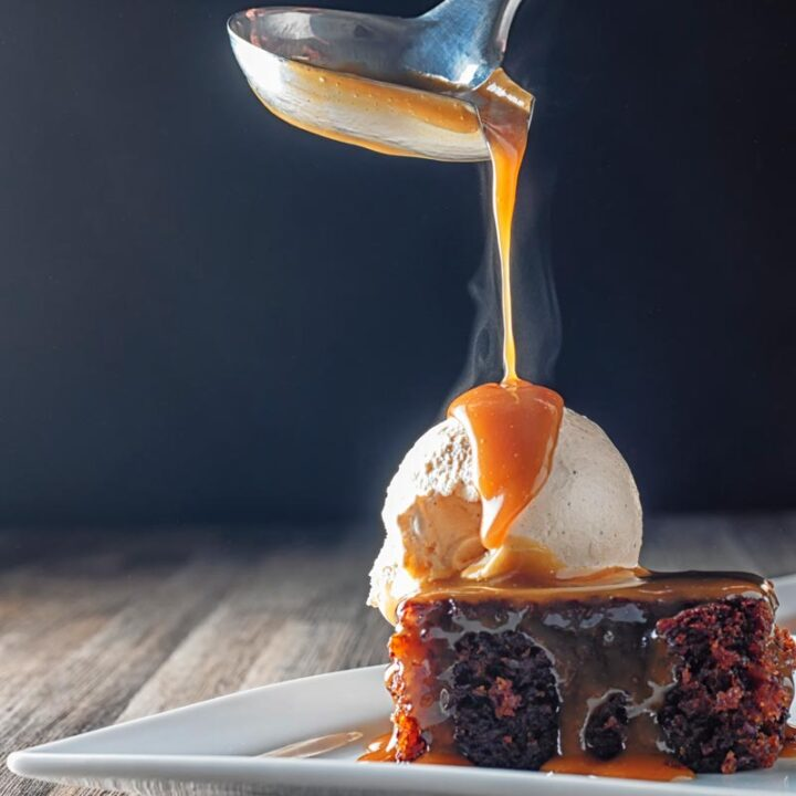 Square image of a steaming hot caramel sauce being poured over a sticky toffee pudding topped with vanilla ice cream