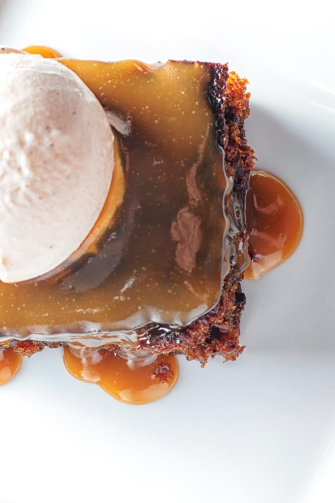 Portrait overhead image of a sticky toffee pudding topped with caramel sauce and vanilla ice cream