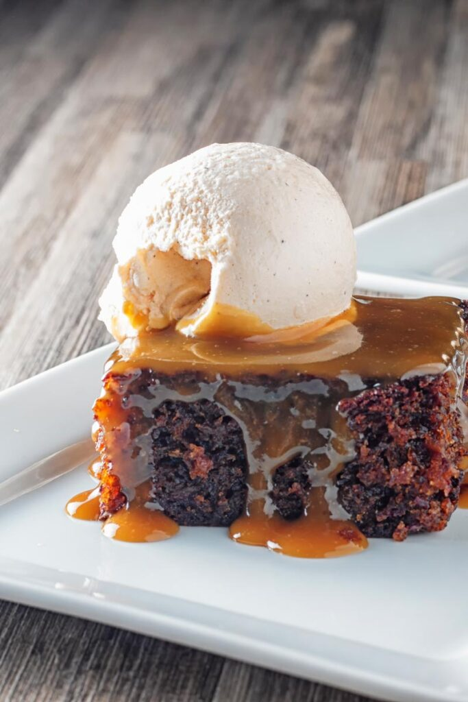 Portrait image of a sticky toffee pudding topped with caramel sauce and vanilla ice cream