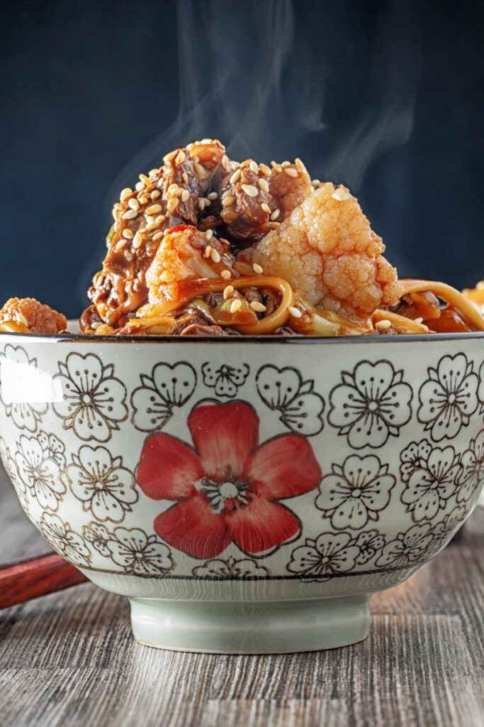 Portrait image of a steaming hot Szechuan beef stir fry with noodles and cauliflower served in an Asian style bowl decorated with a red flower