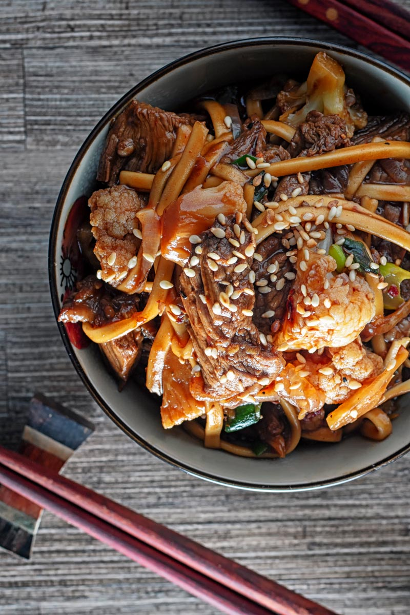 Portrait overhead image of Szechuan beef stir fry with noodles and cauliflower