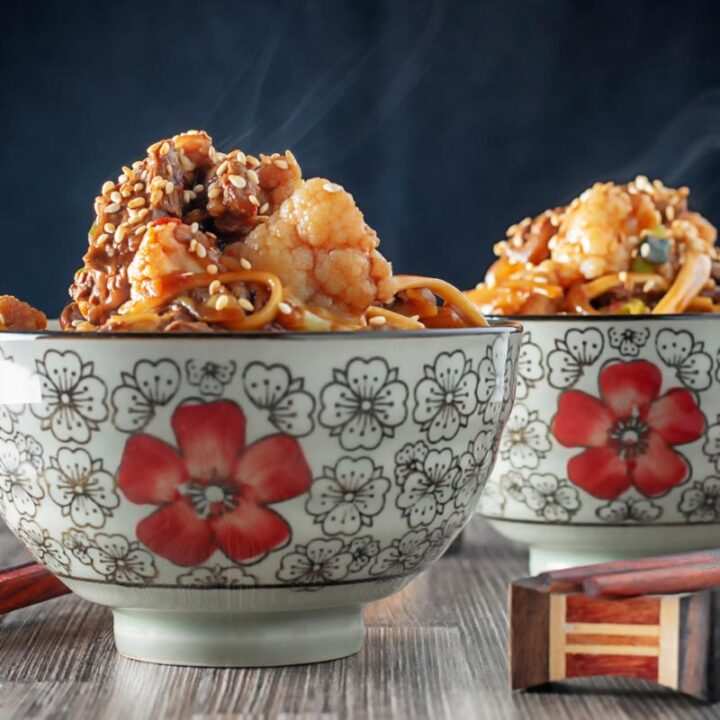 Square image of a steaming hot Szechuan beef stir fry with noodles and cauliflower served in two Asian style bowls decorated with a red flower