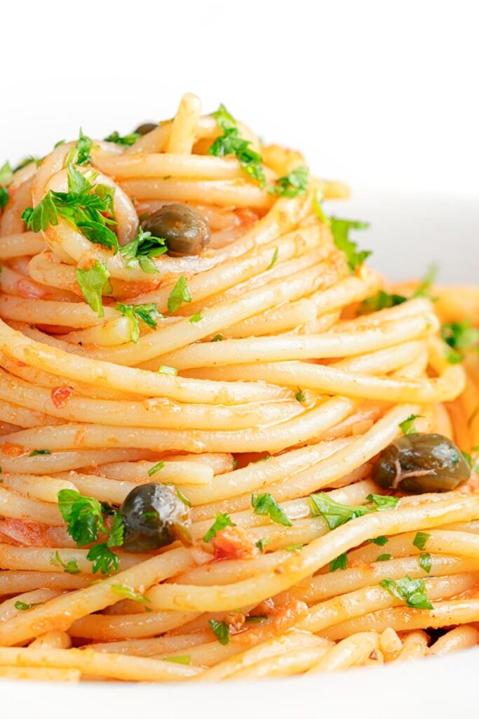 Portrait close up image of a pile caper, tomato and tuna spaghetti