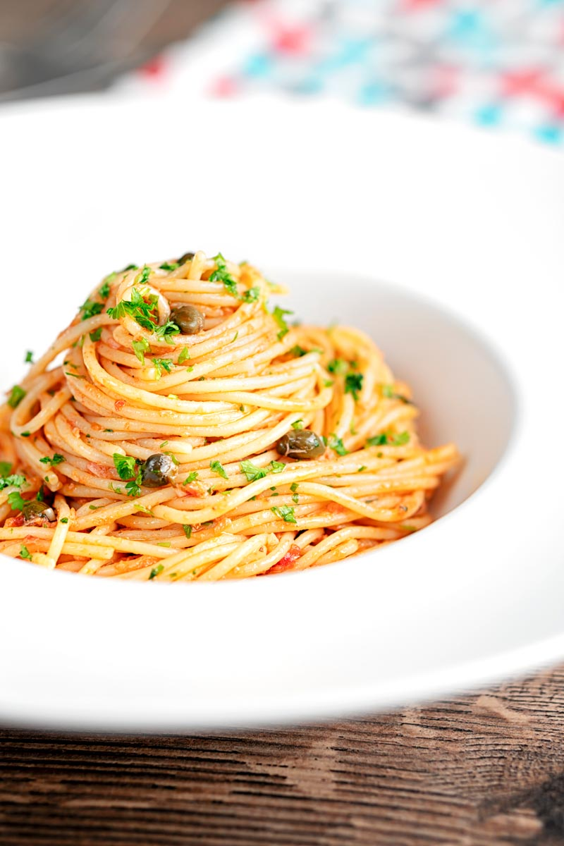 Portrait image of a pile caper, tomato and tuna spaghetti served in a white pasta bowl