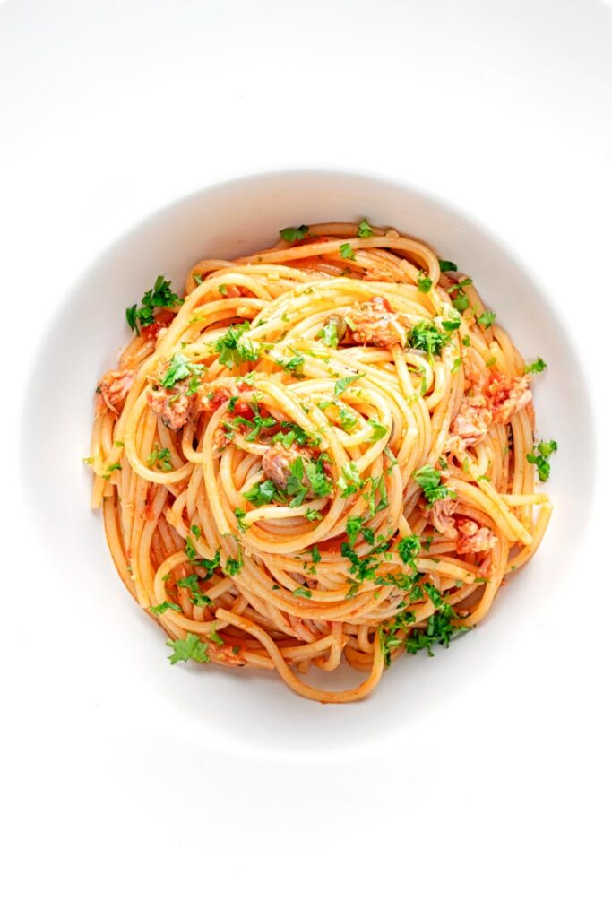 Portrait overhead image of a pile caper, tomato and tuna spaghetti served in a white pasta bowl