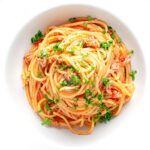 Portrait overhead image of a pile caper, tomato and tuna spaghetti served in a white pasta bowl with text overlay