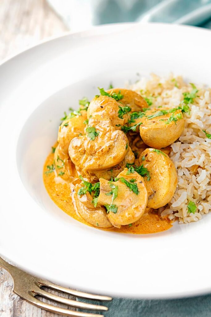 Portrait image of a vegetarian mushroom stroganoff served with wholegrain rice in a white bowl