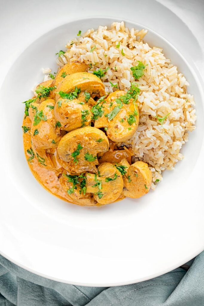 Porrtrait overhead image of a vegetarian mushroom stroganoff served with wholegrain rice in a white bowl