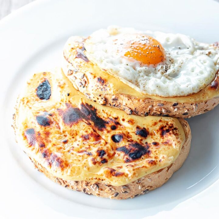 Square image of welsh rarebit with a fried egg, AKA buck rarebit served on a white plate