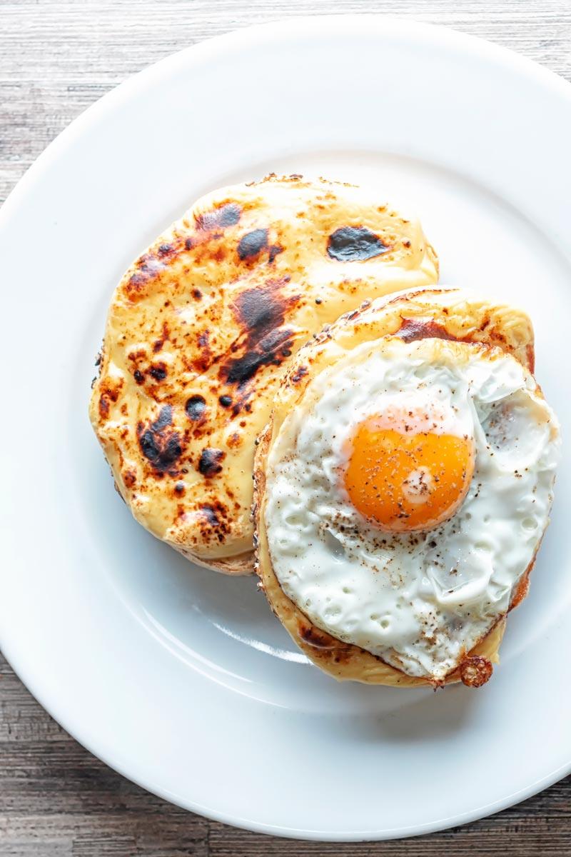 Portrait overhead image of welsh rarebit with a fried egg, AKA buck rarebit served on a white plate
