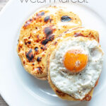 Portrait overhead image of welsh rarebit with a fried egg, AKA buck rarebit served on a white plate with text overlay