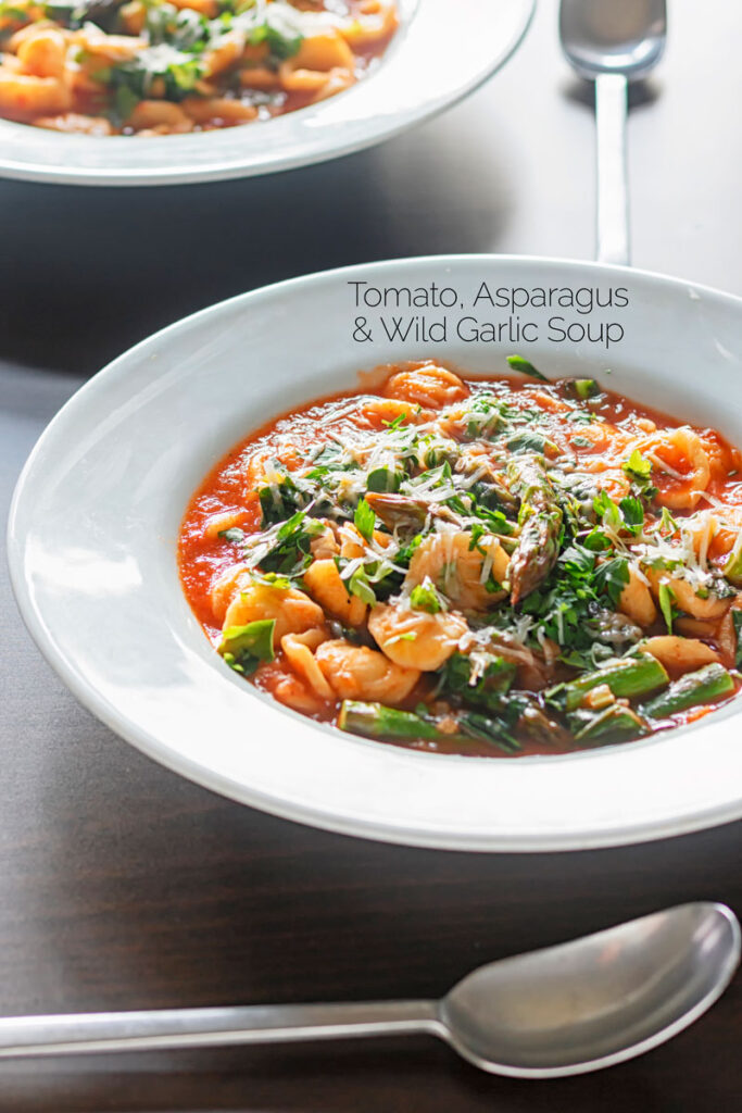 Portrait image of a main course wild garlic, tomato and asparagus soup topped with parmesan cheese and parsley served in a white bowl with text overlay