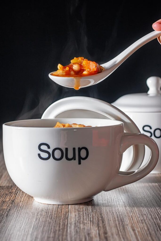 Portrait image of a spoonful of winter vegetable soup being taken a steaming soup cup