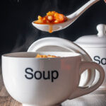 Portrait image of a spoonful of winter vegetable soup being taken a steaming soup cup with text overlay