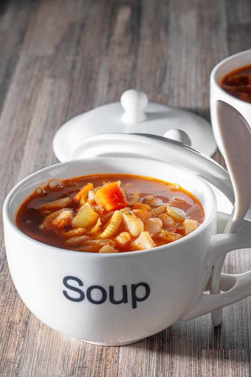 Portrait image of a winter vegetable soup served in a large cup with soup printed on the front