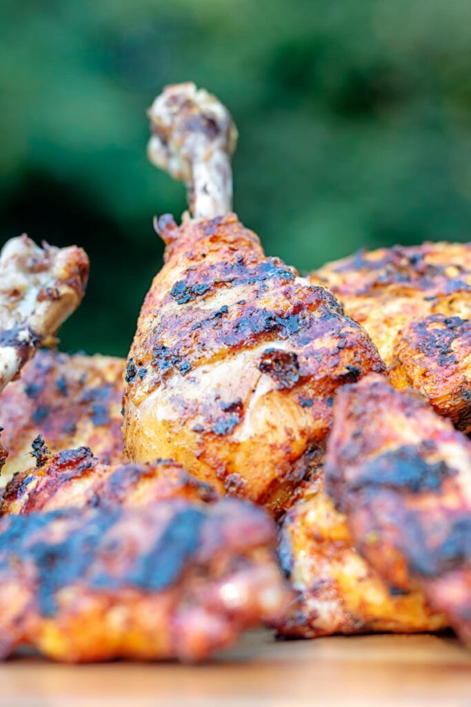 Portrait close up image of a BBQ tandoori chicken drumstick with surrounded by out of focus chicken