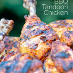 Portrait close up image of a BBQ tandoori chicken drumstick with surrounded by out of focus chicken with text overlay