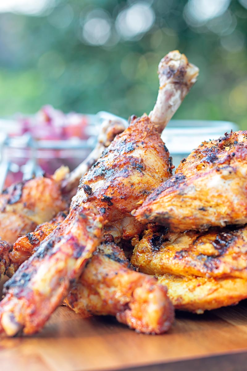 Portrait image of a BBQ tandoori chicken drumstick with surrounded by out of focus chicken
