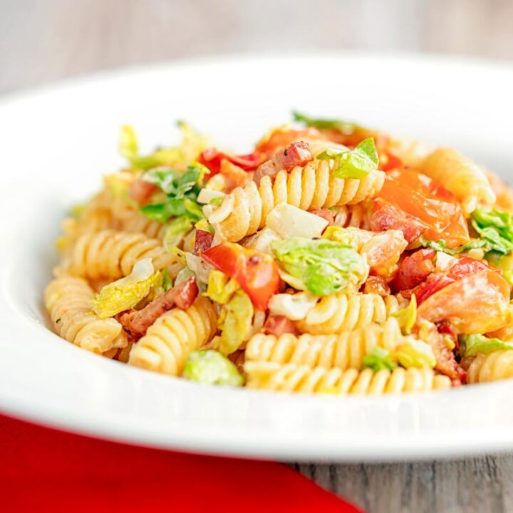 Square image of a BLT pasta salad using fusilli pasta served in a shallow white bowl