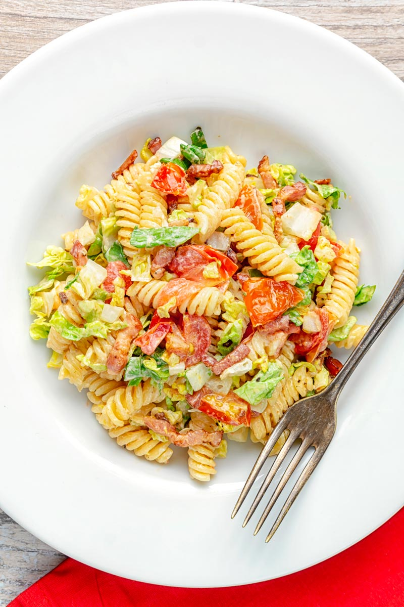 Portrait overhead image of a BLT pasta salad using fusilli pasta served in a shallow white bowl