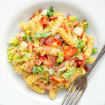 Portrait overhead image of a BLT pasta salad using fusilli pasta served in a shallow white bowl with text overlay