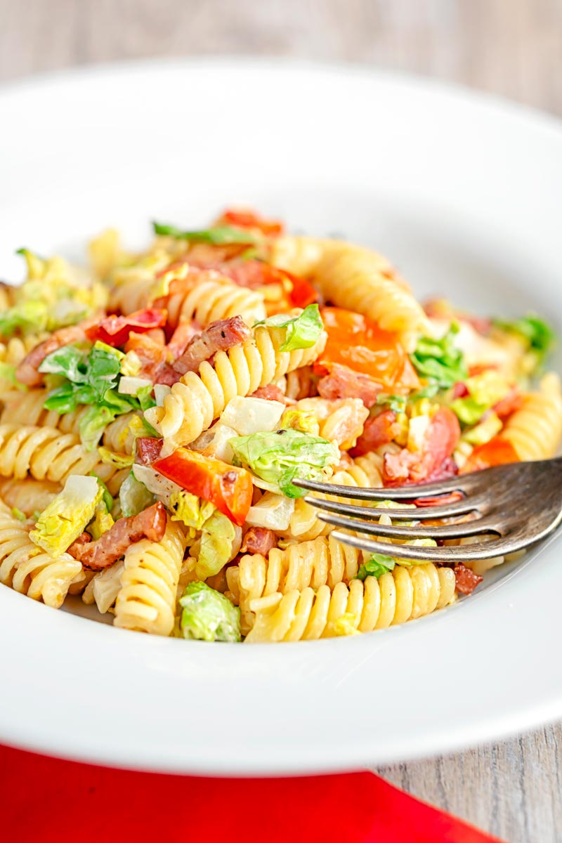Portrait image of a BLT pasta salad using fusilli pasta served in a shallow white bowl