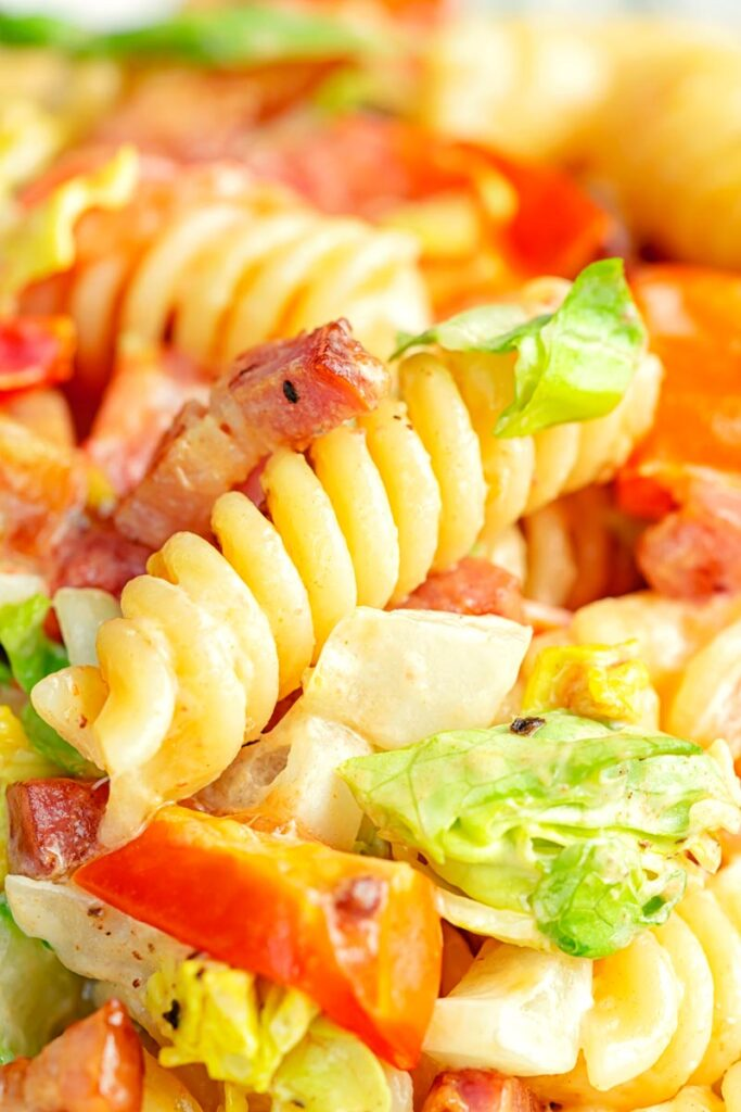 Portrait close up image of a BLT pasta salad using fusilli pasta served in a shallow white bowl