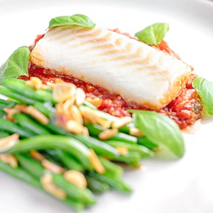 Square image of baked cod fillet on tomato sauce with green beans and fresh basil