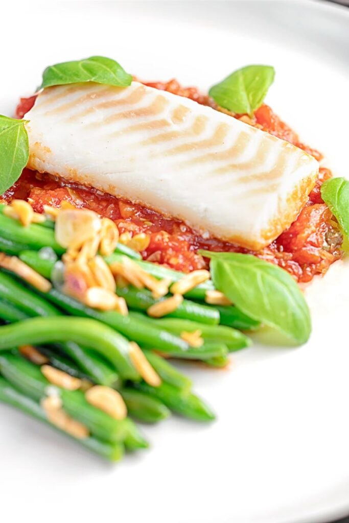 Portrait image of baked cod fillet on tomato sauce with green beans and fresh basil