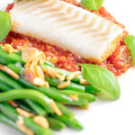Portrait image of baked cod fillet on tomato sauce with green beans and fresh basil with text overlay