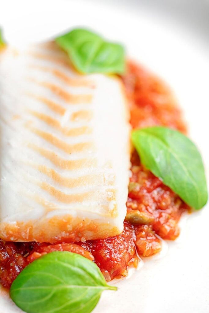 Portrait close up image of baked cod fillet on tomato sauce with green beans and fresh basil