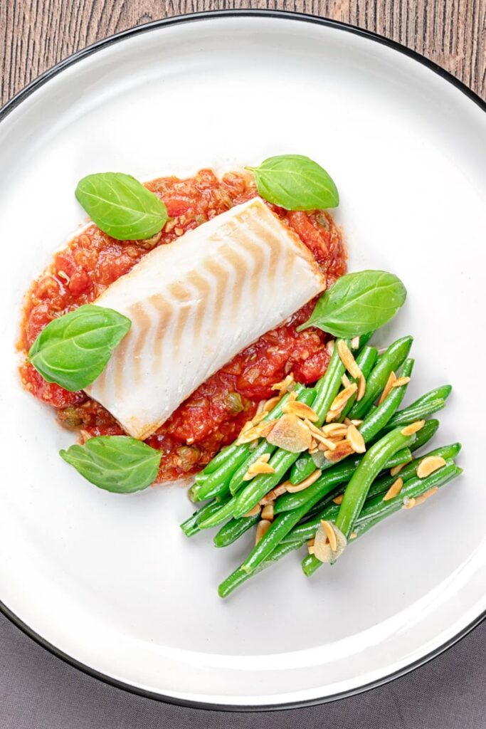 Portrait overhead image of baked cod fillet on tomato sauce with green beans and fresh basil