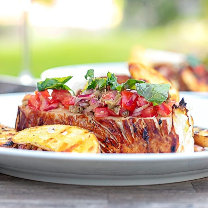 Square image of a balsamic cabbage heart steak served with tomato salad and potato wedges.