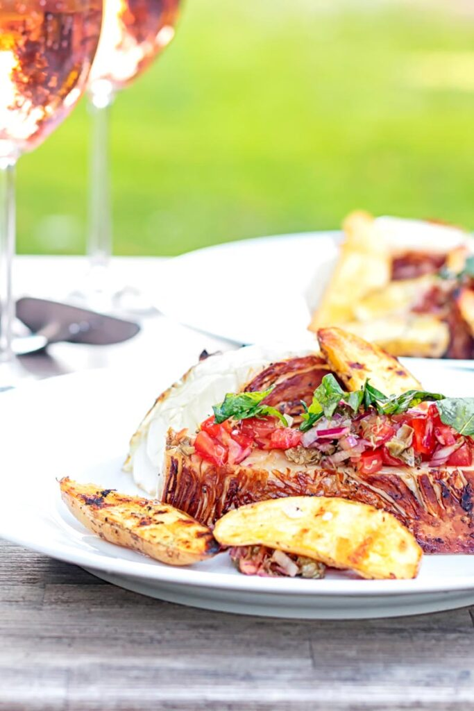 Portrait image of a balsamic cabbage heart steak served with tomato salad and potato wedges.