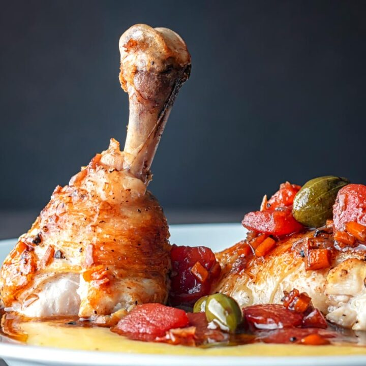 Square image of a chicken leg separated into thigh and drummer with tomatoes and caperberries and a balsamic sauce served on polenta