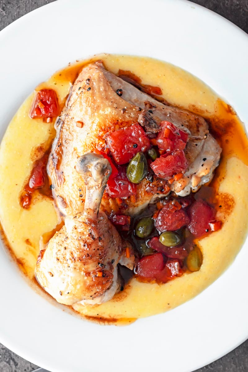 portrait overhead image of a chicken leg separated into thigh and drummer with tomatoes and caperberries and a balsamic sauce served on polenta