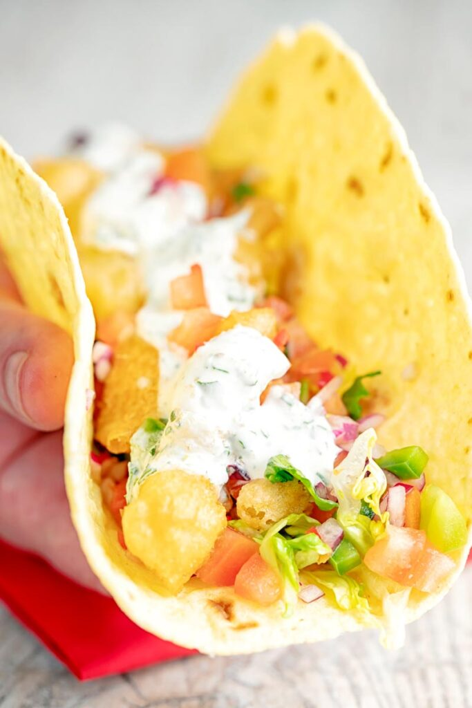 Portrait image of beer battered cod fish tacos served in a corn tortilla with a coriander crema