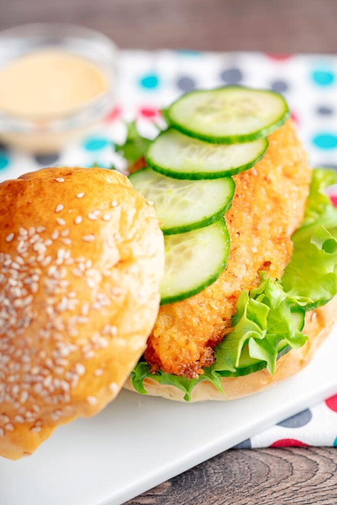 Portrait image of a chicken breast burger with lettuce and cucumber