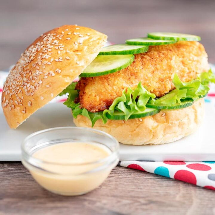 Square image of a chicken breast burger with lettuce and cucumber with a bowl of chilli and lime mayo